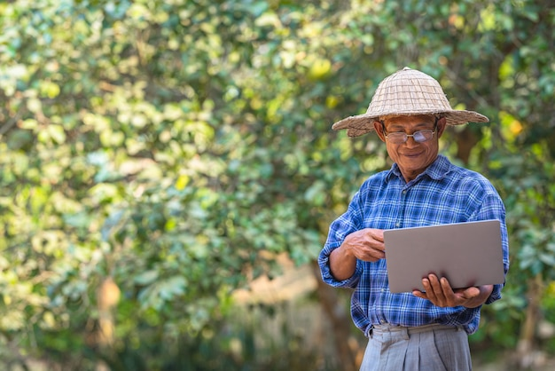 Farmer asian with smartphone and laptop,business and technology concept