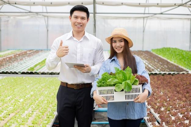 Азиатские женщины-фермеры держат корзины, содержащие только чистые и качественные органические овощи с гидропонной фермы и инспектора по качеству потребителей. владелец фермы из таиланда и инспектор по качеству овощей.