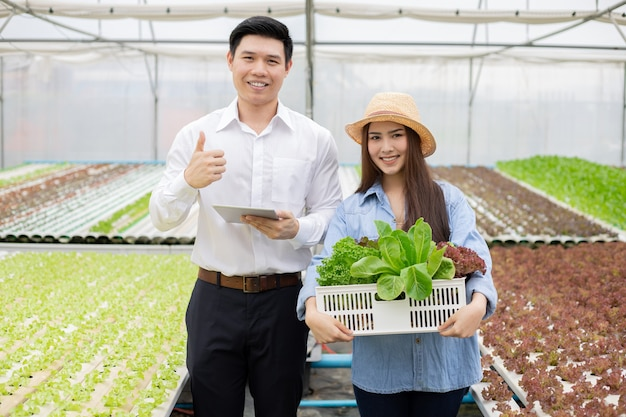 Farmer asian woman hold baskets that contain only clean and quality organic vegetables from hydroponics farm and quality inspector for consumers. thai farm woman owner and vegetable quality inspector.
