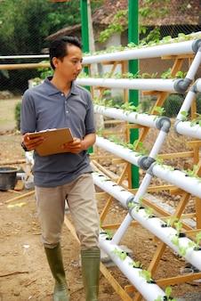 농부는 유기농 채소의 성장을 통제합니다.