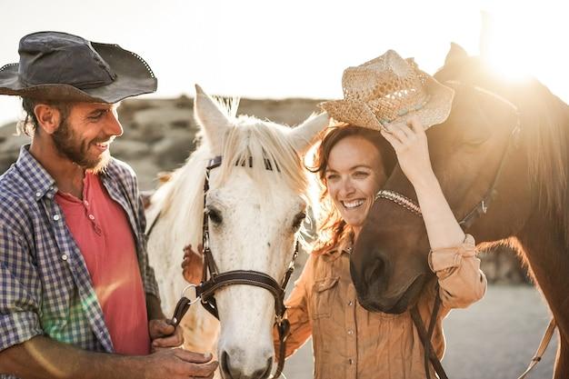 Пара фермеров веселится с бездушными лошадьми в солнечный день в загоне ранчо - основное внимание уделяется правой лошади