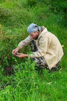 農家が草を掘っています。