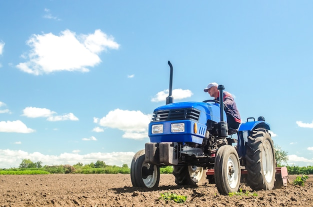 A farmer drives a tractor on a farm field bottom view loosening surface land cultivation