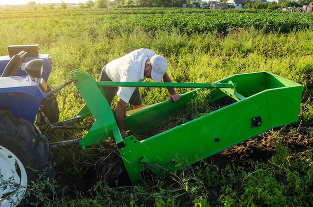 A farmer examines a machine for digging out potato root vegetables. maintenance equipment