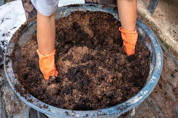 肥料、植物、およびバケツの土から堆肥をシャベルする手袋をはめた農夫の手