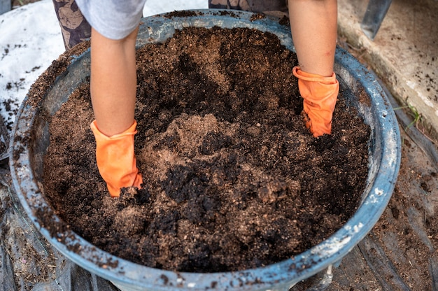 Farmer hand wearing gloves shoveling compost from manure, plant, and soil in bucket