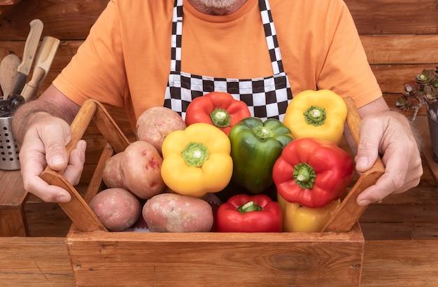 農家の手は、木製のバスケット、ジャガイモとピーマン、栄養と健康的なライフスタイルの上に生野菜を保持します-アクティブな引退した高齢者の概念