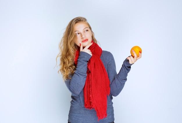 Фермер держит апельсин и планирует сбор урожая.