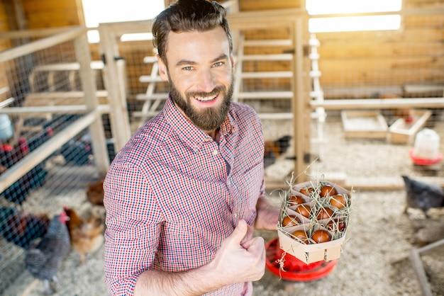 鶏舎の屋内で木製のパックに卵を保持している農家