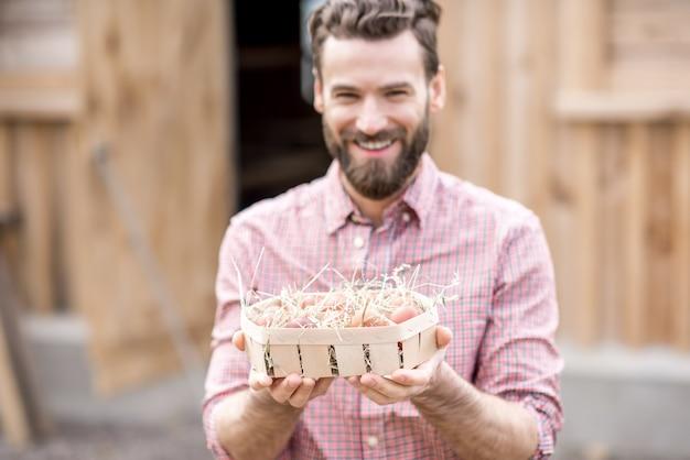 鶏舎の背景に木製パックで卵を保持している農家。卵に焦点を当てた画像