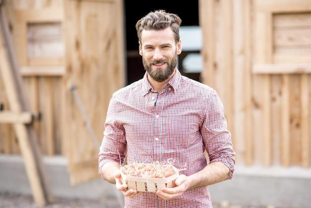 鶏舎の背景に木製パックで卵を保持している農家