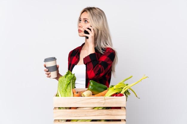 Farmer holding fresh vegetables in a wooden basket