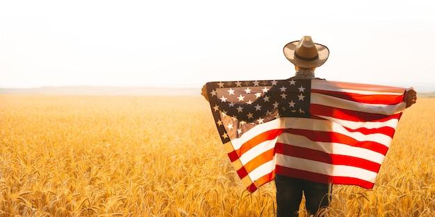 アメリカの国旗を保持している農家