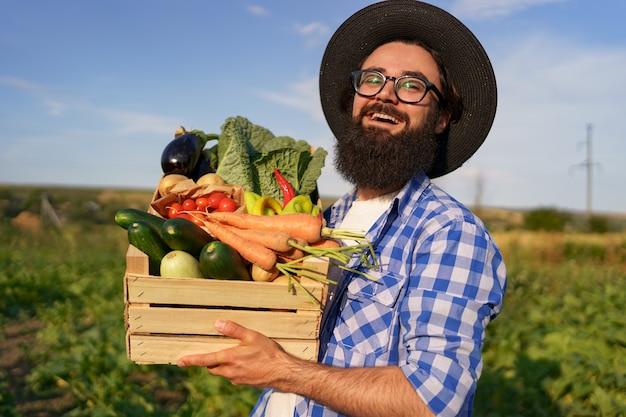 農夫は庭に歩いている間、新鮮な野菜が入った木箱を持っています。有機エコデリバリーの準備