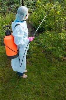 보호복을 입은 농부가 봄 과수원에서 압력 분무기와 화학 물질로 곰팡이 질병이나 해충의 사과 나무를 뿌리고 있습니다.
