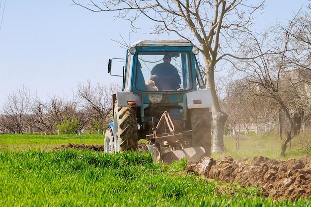 파종을 위한 쟁기로 땅을 준비하는 파란색 트랙터의 농부