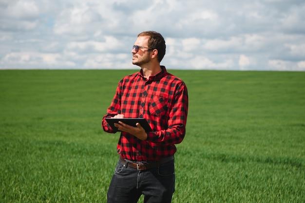 Фермер в красной клетчатой рубашке с помощью планшета на пшеничном поле. применение современных технологий и приложений в сельском хозяйстве. концепция умного сельского хозяйства и агробизнеса