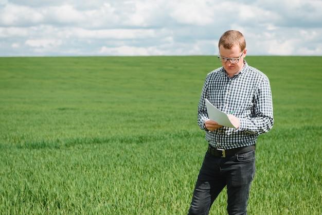 Фермер в красной клетчатой рубашке с помощью планшета на пшеничном поле. применение современных технологий и приложений в сельском хозяйстве