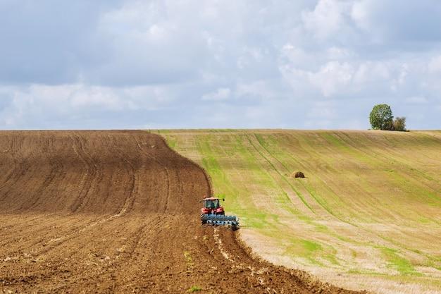 파종을 위해 쟁기와 땅을 준비하는 빨간 트랙터 농부