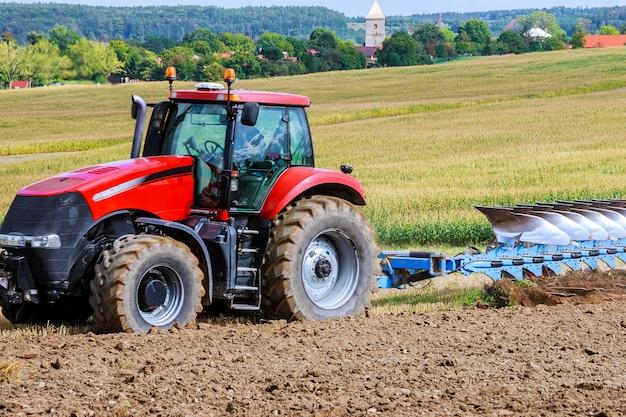 파종을 위한 쟁기로 땅을 준비하는 빨간 트랙터의 농부