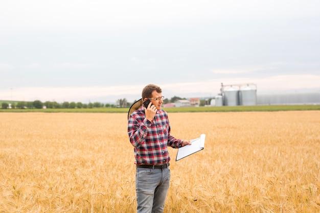 Фермер в зерновой отрасли подсчитывает и контролирует рост пшеницы и ведет телефонный разговор.