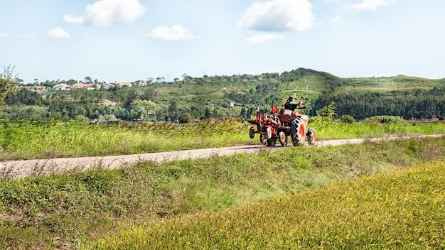 Фермер на урожайном поле машет трактором