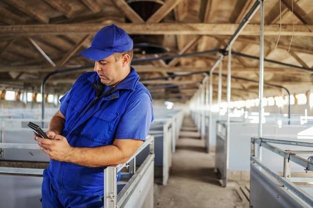 立って傾いている作業服の農夫。彼は動物販売業者に電話するためにスマートフォンを使用しています