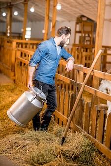 농부는 염소 헛간에서 복고풍 우유 용기와 함께 서 있는 염소를 보고 있습니다. 천연 우유 생산 및 농업