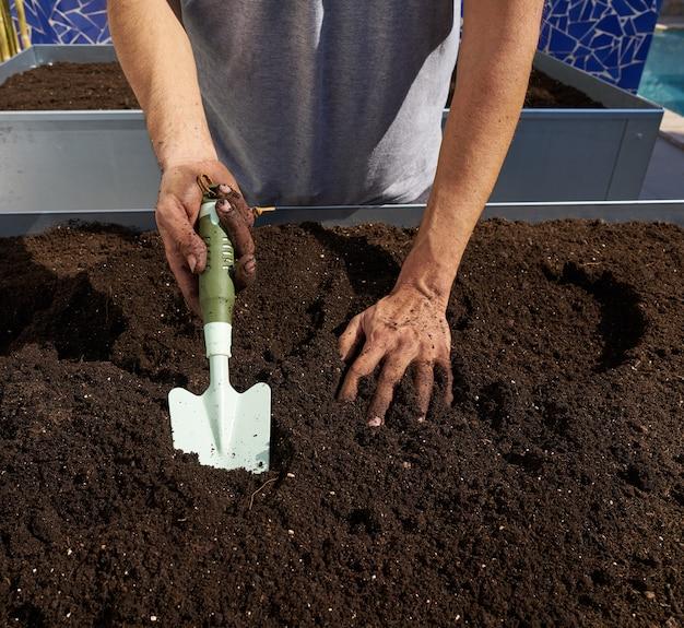 Farmer man hands dirty on substratum
