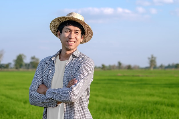 A farmer man wearing a woven hat is standing with his arms crossed and smiling in the field.