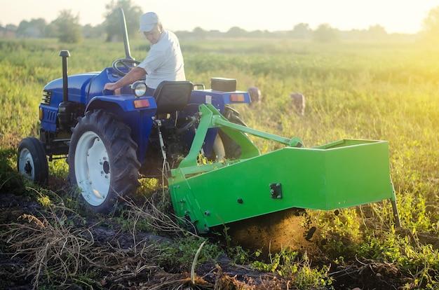 Фермер на тракторе выкапывает картошку из почвы. извлеките корнеплоды на поверхность