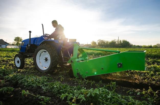 トラクターの農民が早春の農地で最初のジャガイモを収穫するジャガイモを掘り起こす