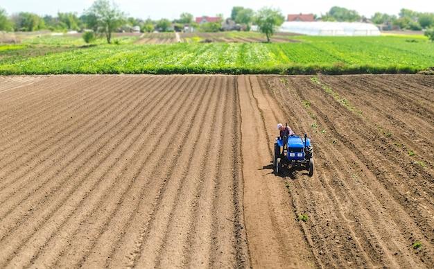 トラクターの農夫は畑を運転します。農業とアグリビジネス。