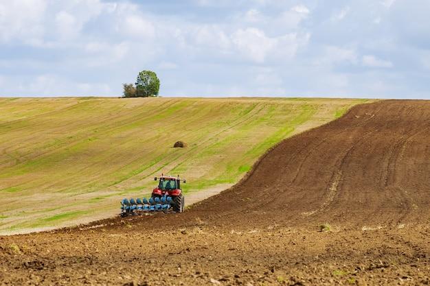 트랙터를 탄 농부가 묘상 경운기로 파종하기 전에 땅을 갈고 있다