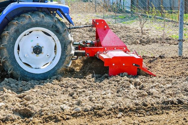 Фермер вспахивает поле. маленький трактор с плугом в поле. выращивание.