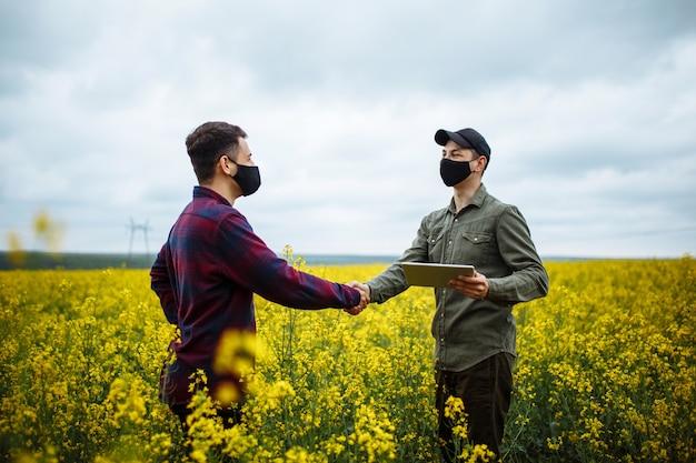タブレットを持って菜種咲く植物に農民の手とフィールドで手を握る