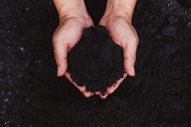 農民の手が土を耕して植え付けの準備をします。