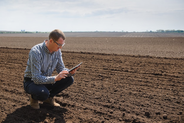 Farmer sitting in a plowed field. agriculture, crop concept