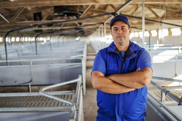 腕を組んで空の納屋に立っている農夫。動物の概念のための納屋を準備している農夫。