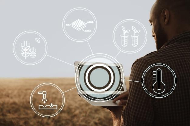 Фермер стоит с цифровым планшетом на пшеничном поле, используя современные технологии в сельском хозяйстве