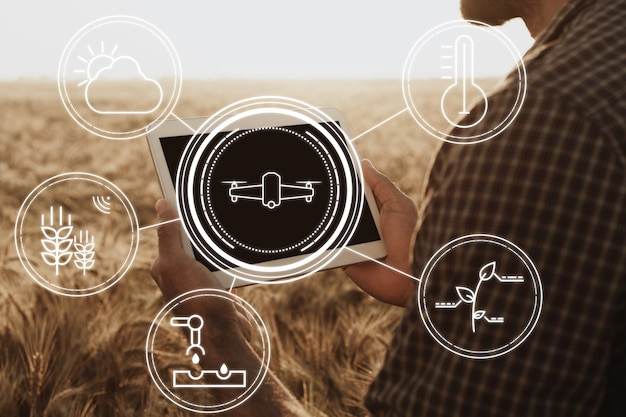Farmer standing with digital tablet in a wheat field using modern technologies in agriculture, close up