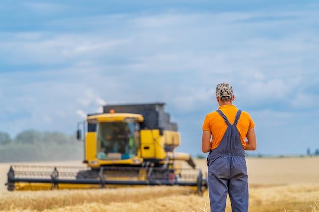 農夫はカメラに背を向けて立っています。農夫の前で黄色いコンバイン。ゴールドドライ小麦。
