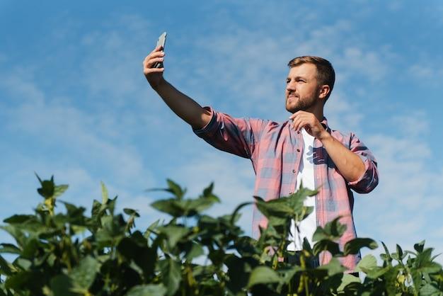 농부가 콩 농장 사진을 찍고 있습니다. 품질 관리. 농업경제학자의 작품. 브라질 농장.