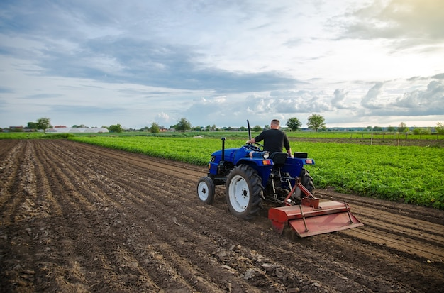 Farmer on tractor cultivates farm field milling soil crumbling ground before cutting rows