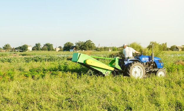 A farmer on a tractor digs potatoes in the farm field. countryside. food production