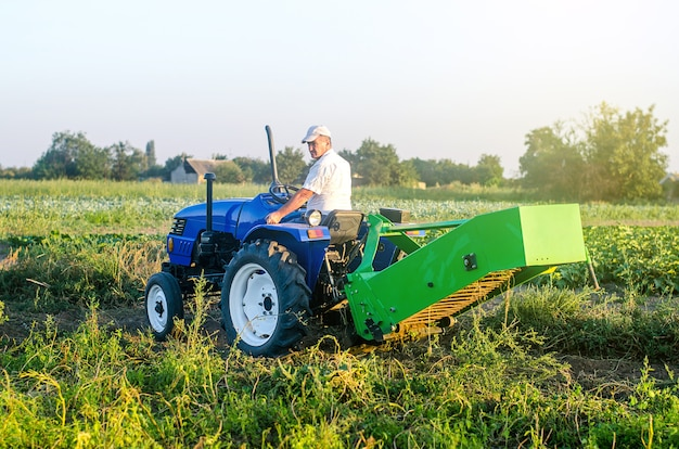 A farmer on a tractor with an aggregate of equipment for digging out potato
