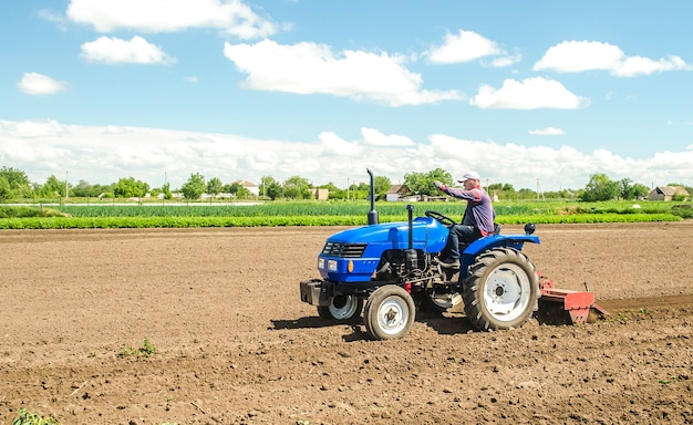 A farmer on a tractor with a mill unit crushes and processes the soil for further sowing