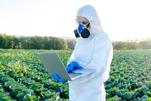Farmer wearing white protective suit  chemical mask and glasses uses laptop on farm field