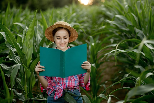 Фермер с папкой стоит на кукурузном поле и проверяет рост овощей. сельское хозяйство - производство продуктов питания, концепция урожая.