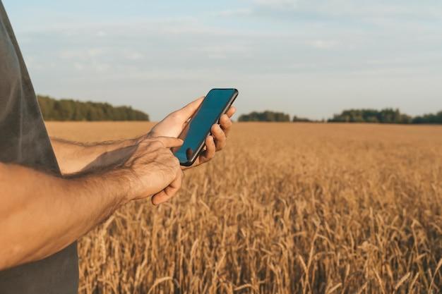 麦畑を背景にスマートフォンを手にした農夫